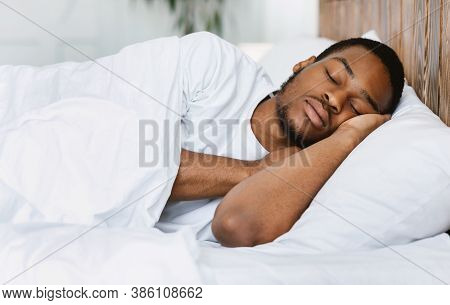 Asleep African American Guy Sleeping Resting Peacefully In His Comfortable Bed At Home, Lying With E