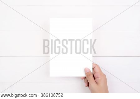 Hand Of Young Man Holding Poster Or Card Or Brochure With White Paper Blank On Wooden Table, Greetin