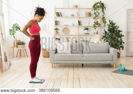 Weight-loss Problem. Frustrated Black Girl Standing On Weight-scales Having A Hard Time Slimming, Ga