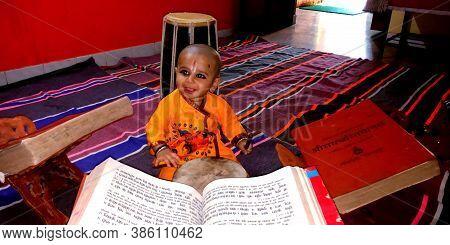 District Katni, India - January 15, 2019: Hindu Religious Little Kid Priest Seating With Ramayana Ho