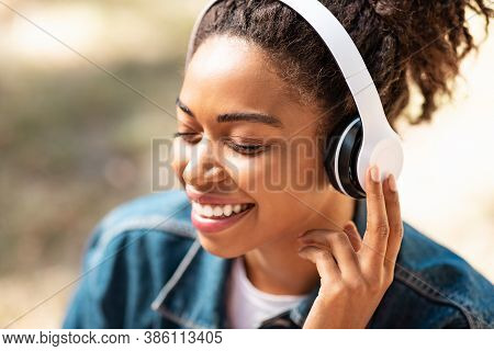 Portrait Of Happy Relaxed Black Lady In Headphones Listening To Music Relaxing Sitting With Eyes Clo