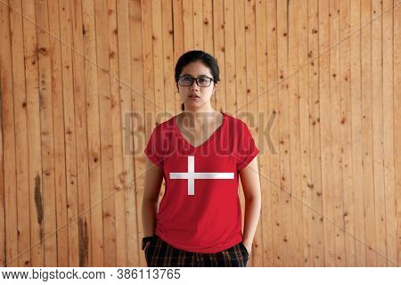 Woman Wearing Denmark Flag Color Shirt And Standing With Two Hands In Pant Pockets On The Wooden Wal