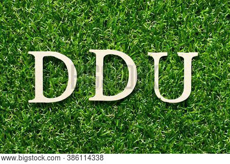 Wood Alphabet Letter In Word Ddu (abbreviation Of Delivered Duty Unpaid) On Green Grass Background