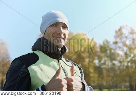 Middle Aged Sportsman Showing Thumbs Up And Smiling. Man Getting Rest After Jogging. Handsome Man We