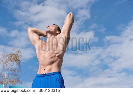 Middle Aged Toned Body Man Stands Shirtless Under Sunlight And Getting Rest After Workout. Outdoors