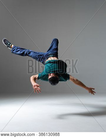 Stylish Young Guy Breakdancer Jumps Dancing Hip-hop Isolated On Gray Background. Breakdance Lessons