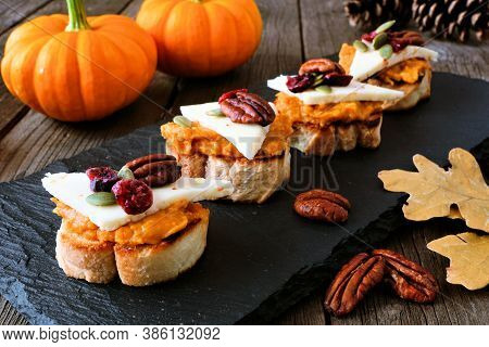 Autumn Crostini Appetizers With Pumpkin Spread, Cheese And Nuts. Side View Serving Scene On A Dark B