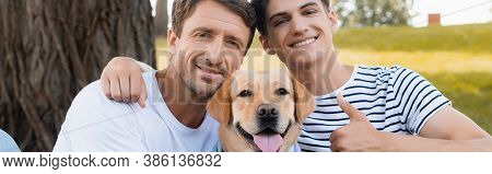 Panoramic Crop Of Teenager Son Showing Thumb Up While Hugging Father Near Golden Retriever