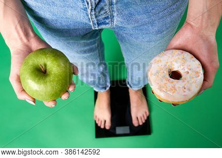 Top View Of Female Legs In Jeans Standing On A Scales. Woman Is Holding A Green Apple And Greasy Don
