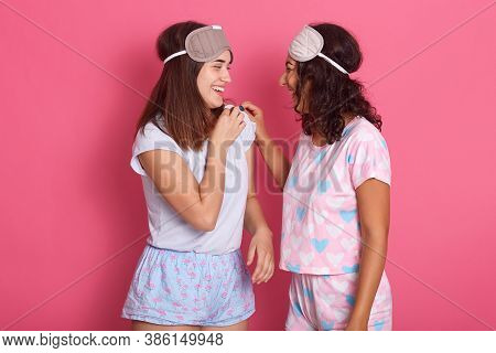 Two Girlfriends Gossiping Against Pink Wall, Ladies In Pajamas And Blindfolds, Friends Looking At Ea