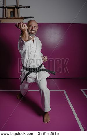 Karate Master In Powerful Position, Practicing Martial Arts In His Dojo