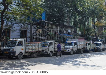 Kolkata, India - February 1, 2020: An Unidentified Man Walks Past Several Parked Semi Trucks On The