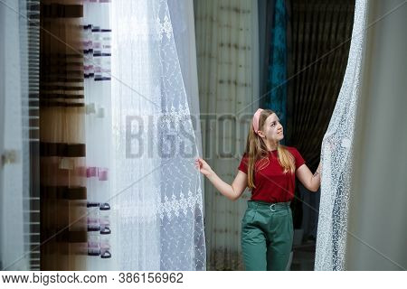 Young Woman Choosing Fabric For New Curtains In A Store. Samples Of The Curtain Hang On Hangers On A