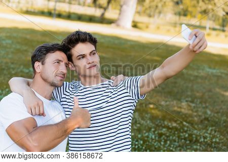 Father Showing Thumb Up And Teenager Son Taking Selfie In Park