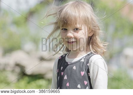 Child Portrait Of Cute Blond Hair Smiling Little Girl Outdoors.