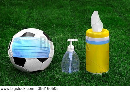 A Soccer Ball, Football With A Face Mask, Hand Sanitizer And Disinfecting Wipes On A Green Grass. Co
