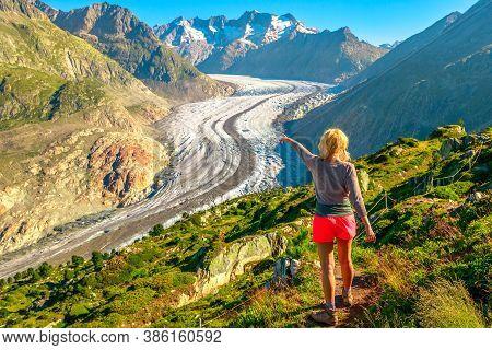 Aletsch Glacier From Moosfluh Viewpoint In Summer, Valais Canton, Switzerland, Europe. Tourist Hiker