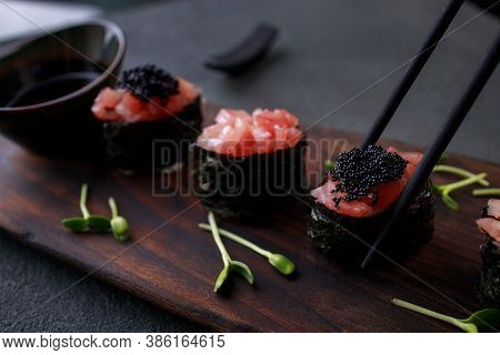 Eating Sushi. Chopsticks Taking Salmon Gunkan Maki Roll From Plate. Japanese Food, Deluxe Restaurant