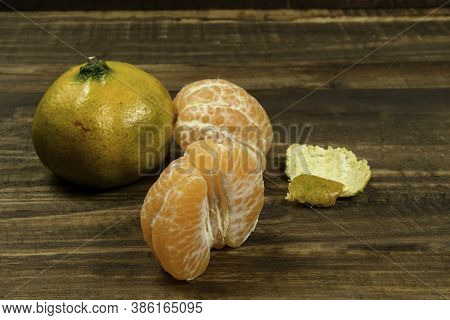 Peeled Tangerine In A Wooden Rustic Table