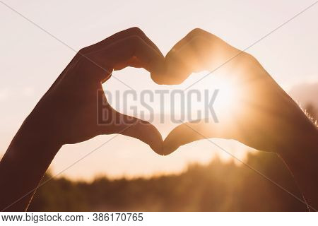 Hand Shape Heart Against Beautiful Sunset With Sun Flare