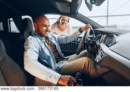 Joyful Young Couple Looking Around Inside A New Car They Are Going To Buy In A Car Shop