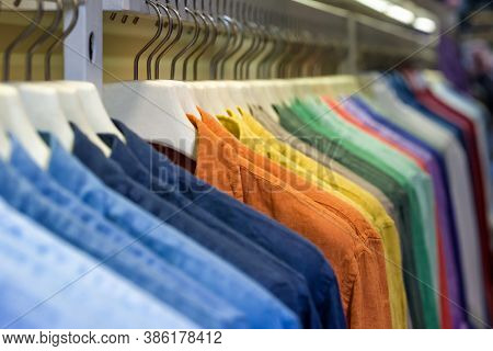 Bright colorful cotton shirts on hanger in boutique shop close up. Fashion clothes on clothing rack. Rainbow color choice of trendy male wear on hangers in store closet or Summer wardrobe concept.