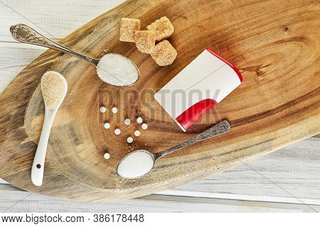 Sugar Substitute Tablets And Natural Sweetener In Powder And Brown, White And Diced Sugar On A Woode