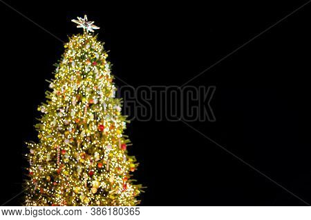 Unfocused Christmas Tree With Lights Decorations Outdoors At Night.