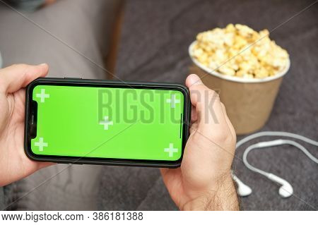 Close Up Mans Hand Holding A Mobile Phone With Xxx Logo With Apple Earphones And Popcorn Box Next To
