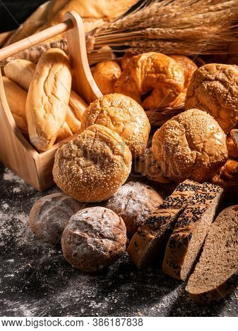 Close-up A Group Of Bread On The Black Wooden Table With Sunlight In The Morning. Top View Freshness