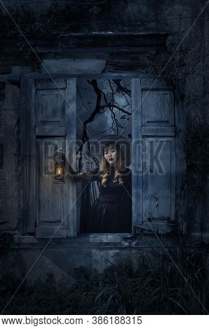 Halloween Witch Holding Ancient Lamp Standing In Old Damaged Wood Window With Wall Over Church, Bird