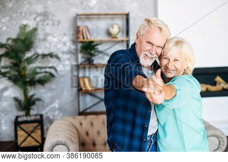 Joyful Elderly Couple Has Fun In The Cozy Living Room. A Happy Senior Wife And Husband Are Dancing A