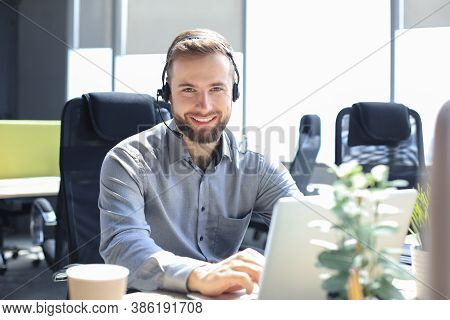 Smiling Male Call-center Operator With Headphones Sitting At Modern Office, Consulting Online Inform