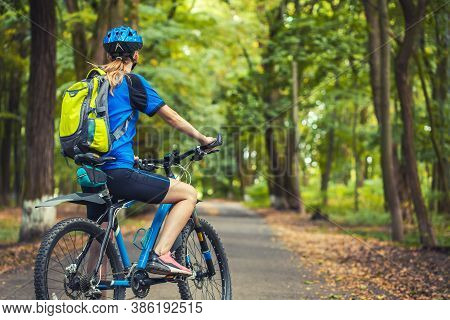 Woman Cyclist Rides Mountain Bike Forest Trails.