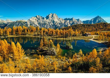 Beautiful Colorful Autumn Forest With Majestic Alpine Lake. Colorful Larches And Small Cute House On