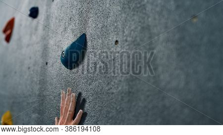 Close Up Of A Hand Of Woman Climbing Up On Rock Wall In Gym. Bouldering Training Concept. Focus On F