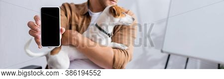 Partial View Of Businessman Showing Smartphone With Blank Screen While Holding Jack Russell Terrier