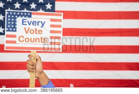 Hands Holding Every Vote Counts Sign Board With Us Flag As Background With Copy Space - Concept Of V