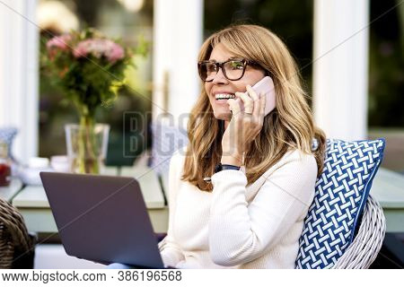 Portrait Shot Of Happy Mature Woman Using Notebook And Talking With Somebody On Her Mobile Phone Whi