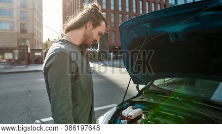 Young Man Looking Confused While Standing Near His Broken Down Car With Open Hood On The City Street