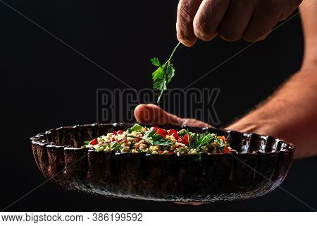 Tabbouleh Salad In The Hands Of The Chef. Middle Eastern Or Arab Dish. Levantine Vegetarian Salad Wi