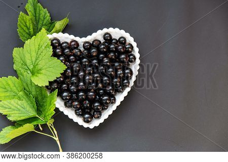 Black Currant Berries In A White Plate In The Form Of A Heart On A Black Background.