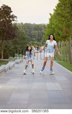 Young Attractive Mother And Her Little Daughter Rollerskating In Summer Park. Happy Family Have Fun