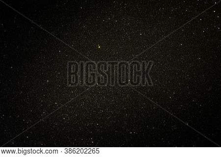 Black Texture With Micro-relief And Glitter. Black Glitter Texture With Illuminated Center