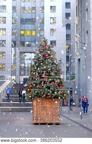 Christmas Tree Decorated With Bright Balls And Toys Stands In Front Of The Entrance To The Office Ce