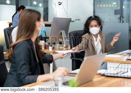 Group of interracial business worker team wear protective face mask in new normal office with social distance practice with hand sanitiser alcohol gel on table prevent coronavirus COVID-19 spreading