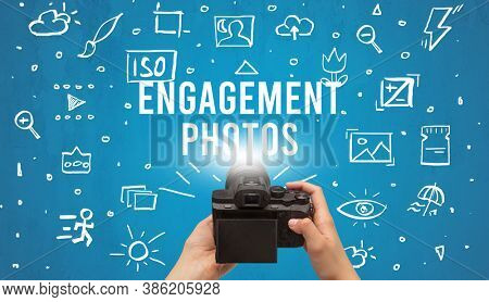 Hand taking picture with digital camera and ENGAGEMENT PHOTOS inscription, camera settings concept