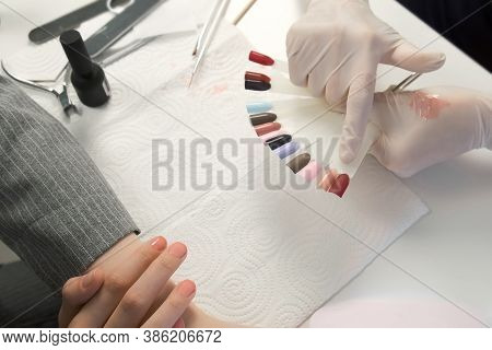 Woman Client Is Choosing Colour From Colourful Nails Tips In Manicure Salon, Closeup View. Manicure