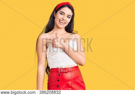 Brunette teenager girl wearing elegant look cheerful with a smile of face pointing with hand and finger up to the side with happy and natural expression on face