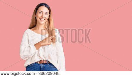 Beautiful young woman wearing casual clothes cheerful with a smile of face pointing with hand and finger up to the side with happy and natural expression on face